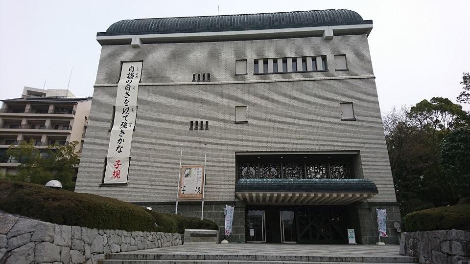 子規記念博物館の外観。「白梅の白きを以て強きかな」の句が書かれている。