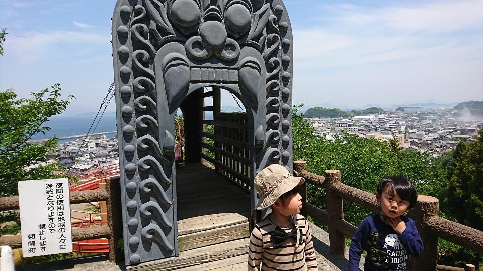 ローラー滑り台の乗り込み口にも鬼瓦が建っている。鬼瓦の前には娘と息子が立つ。
